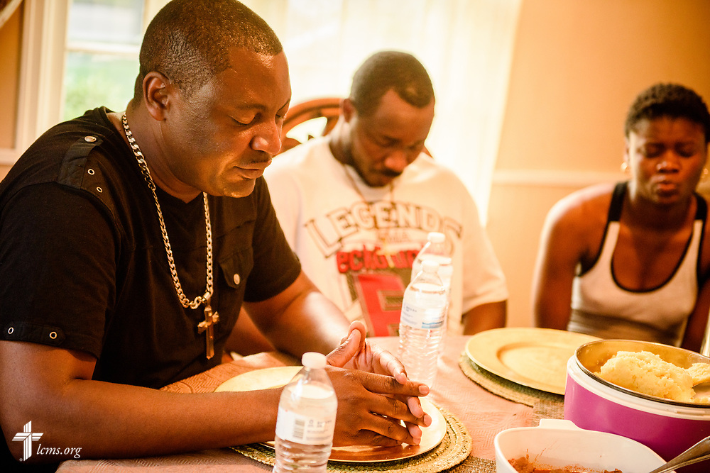 The Rev. Gui Kasongo Kabeo (left), pastor at Eglise Lutherienne Internationale de Sion (International Lutheran Church of Zion) and Gospel Lutheran Church, both in Milwaukee, Wis., prays before dinner at his home on Monday, Aug. 14, 2017 in Milwaukee. Kabeo houses refugees who do not have a place to go when they arrive in the United States. LCMS Communications/Erik M. Lunsford