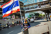 """20 DECEMBER 2013 - BANGKOK, THAILAND: An anti-government protestor at a roadblock to prevent cars from traveling on Silom Road. Thousands of anti-government protestors, supporters of the so called Peoples Democratic Reform Committee (PRDC), jammed the Silom area, the """"Wall Street"""" of Bangkok, Friday as a part of the ongoing protests against the caretaker government of Yingluck Shinawatra. Yingluck dissolved the Thai Parliament earlier this month and called for national elections on Feb. 2, 2014. The protestors want the elections postponed and the caretaker government to step down. The Thai election commission ruled Friday that the election would go on dispite the protests.          PHOTO BY JACK KURTZ"""