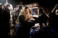 Lampedusa, Italia - 14 marzo 2011. Un immigrato avvolto in una termocoperta per proteggersi dal freddo mentre attende di sbarcare sull'isola di Lampedusa. Un flusso lento ma continuo di sbarchi di immigrati ha portato il CIE (Centro Identificazione ed Espulsione) dell'isola al collasso..Ph. Roberto Salomone Ag. Controluce.ITALY - An immigrant keeps warm with a thermo-sheet before desembarking on the italian island of Lampedusa on March 14, 2011. The temporary accomodation center of the island struggles to give hospitality to all the immigrants that have reached the shores of Lampedusa.