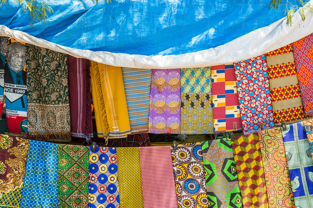 Colorful textiles hung in a row in outdoor marketplace, Chobe National Park - Botswana