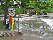 Family obeying a Do Not Cross sign  while watching floodwaters at a low water crossing in Breckenridge Park, San Antonio, Texas.