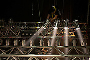 Stage hand of the rock band Status Quo adjusts overhead lights high above the stage while on European tour at in Lille, France.