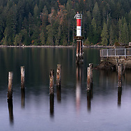 A small lighthouse at Barnet Marine Park on Burrard Inlet in Burnaby, British Columbia, Canada. The cement structure on the right is the remains of the old scrap burner for a lumber mill that used to be on the site until 1958.
