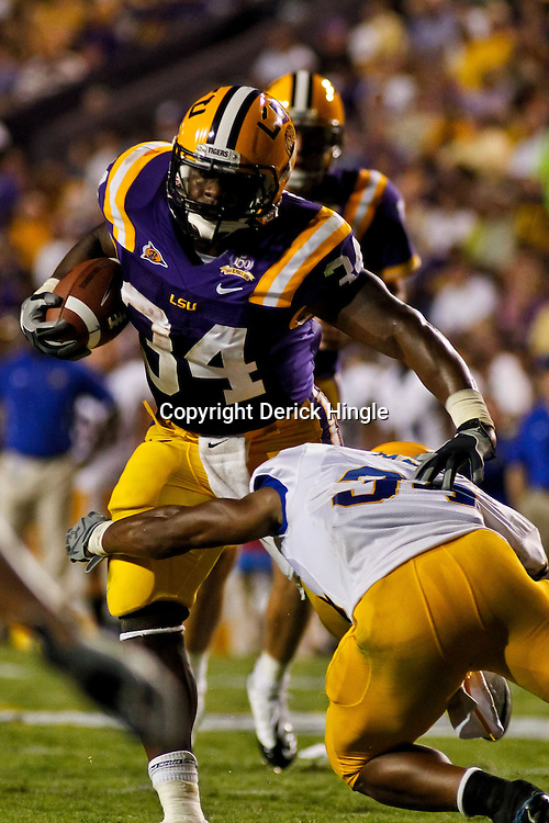 October 16, 2010; Baton Rouge, LA, USA; LSU Tigers running back Stevan Ridley (34) is tackled by McNeese State Cowboys safety Malcolm Bronson (34)during a game at Tiger Stadium. LSU defeated McNeese State 32-10. Mandatory Credit: Derick E. Hingle