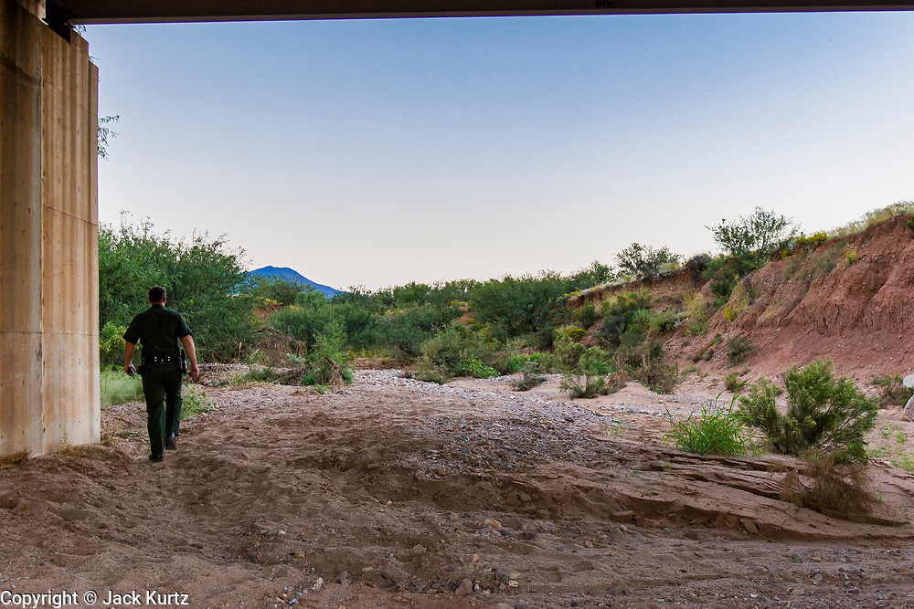 04 OCTOBER 2005 - NACO, AZ: A Border Patrol agent walks through a dry wash under an Arizona highway in the desert near Naco, AZ.     PHOTO BY JACK KURTZ