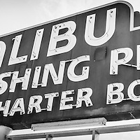 Malibu Pier sign panoramic black and white photo. The famous Malibu Sport Fishing Pier sign is along Pacific Coast Highway in Malibu California in the United States.