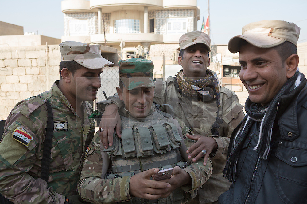 Licensed to London News Pictures. 11/11/2016. Mosul, Iraq. Soldiers, belonging to the Iraqi Army's 9th Armoured Division, relax during a visit to Mosul's Hay Intisar district on the south east of the city. The district was taken by Iraqi Security Forces (ISF) around a week ago and, despite its proximity to ongoing fighting between ISF and ISIS militants, many residents still live in the settlement.<br /> <br /> The battle to retake Mosul, which fell June 2014, started on the 16th of October 2016 with Iraqi Security Forces eventually reaching the city on the 1st of November. Since then elements of the Iraq Army and Police have succeeded in pushing into the city and retaking several neighbourhoods allowing civilians living there to be evacuated - though many more remain trapped within Mosul.  Photo credit: Matt Cetti-Roberts/LNP