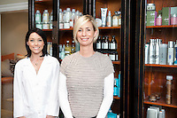 Portrait of beautiful owner with employee standing in front of cosmetic products
