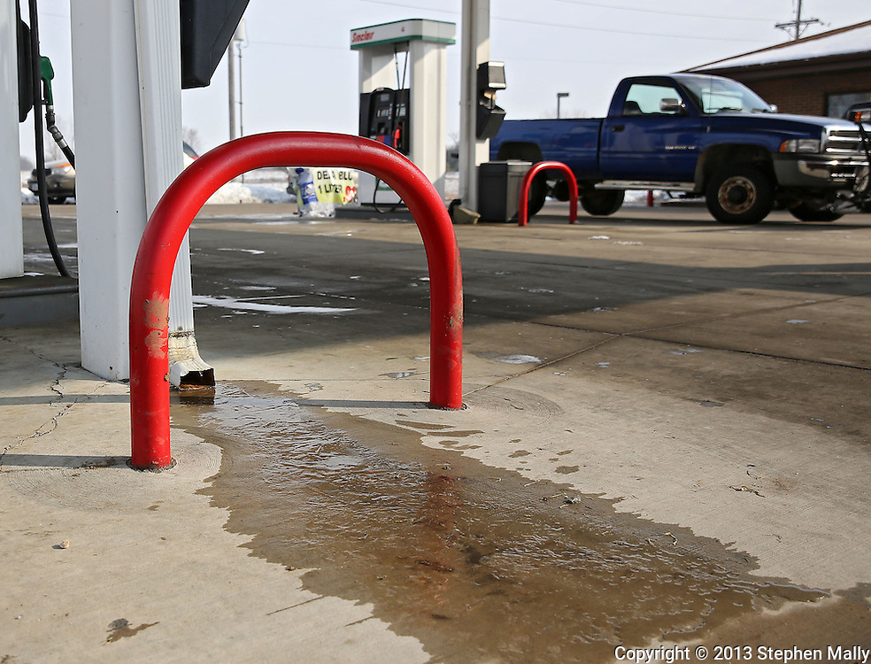 Ice forms from a down-spout by a pump without a SlickShield installed at Hawkeye Convenience Store in Hiawatha on Monday, February 25 2013.