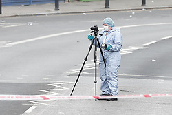 © Licensed to London News Pictures. 06/07/2019. London, UK. A police scenes of crime forensics officer looks for evidence on the Harrow Road near Wembley Stadium after a man was shot on Friday night. The victim, believed to be a man in his 30s, was found with fatal gun shot wounds at 8pm near a mosque. No arrests have so far been made. Photo credit: Peter Macdiarmid/LNP