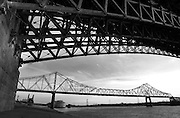 "The Martin Luther King Bridge (formerly known as the Veterans Bridge) is seen below the arch of the Eads Bridge in St. Louis. The MLK Bridge is a cantilever truss bridge of about 4000 feet in total length across the Mississippi River, connecting St. Louis with East St. Louis, Illinois. The bridge serves as traffic relief connecting the multiplexed freeways of Interstate 55, Interstate 70, Interstate 64, and U.S. Highway 40 with the downtown streets of St. Louis..The Eads Bridge is a combined road and railway bridge over the Mississippi River at St. Louis, connecting St. Louis and East St. Louis, Illinois..The bridge is named for its designer and builder, Captain James B. Eads. When completed in 1874, the Eads Bridge was the longest arch bridge in the world, with an overall length of 6,442 feet (1,964 m). The ribbed steel arch spans were considered daring, as was the use of steel as a primary structural material: it was the first such use of true steel in a major bridge project.[1].The Eads Bridge was also the first bridge to be built using cantilever support methods exclusively, and one of the first to make use of pneumatic caissons. The Eads Bridge caissons, still among the deepest ever sunk, were responsible for one of the first major outbreaks of ""caisson disease"" (also known as ""the bends""). Fifteen workers died, two other workers were permanently disabled, and 77 were severely afflicted.[2].The bridge was owned and operated by the Terminal Railroad Association of St. Louis from the 1890s until 1989 when it was swapped for the MacArthur Bridge (St. Louis).[3].The Eads Bridge is still in use, and stands on the St. Louis riverfront between Laclede's Landing on the north and the grounds of the Gateway Arch to the south. Today the road deck has been restored, allowing vehicle and pedestrian traffic to cross the river. The rail deck has been in use for the St. Louis Metrolink light rail line since 1993.  Photo by Lance Cheung"