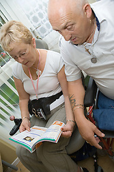 Couple looking at a book about accessible places to stay in Britain and planning their holiday,