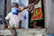 Aminata Nombre, 34, gives her 20-month-old son Ali Souleni some water to drink at their home in the Campement neighborhood of Abidjan, Cote d'Ivoire on Wednesday July 10, 2013. Aminata is under ARV treatment and takes three pills every day.