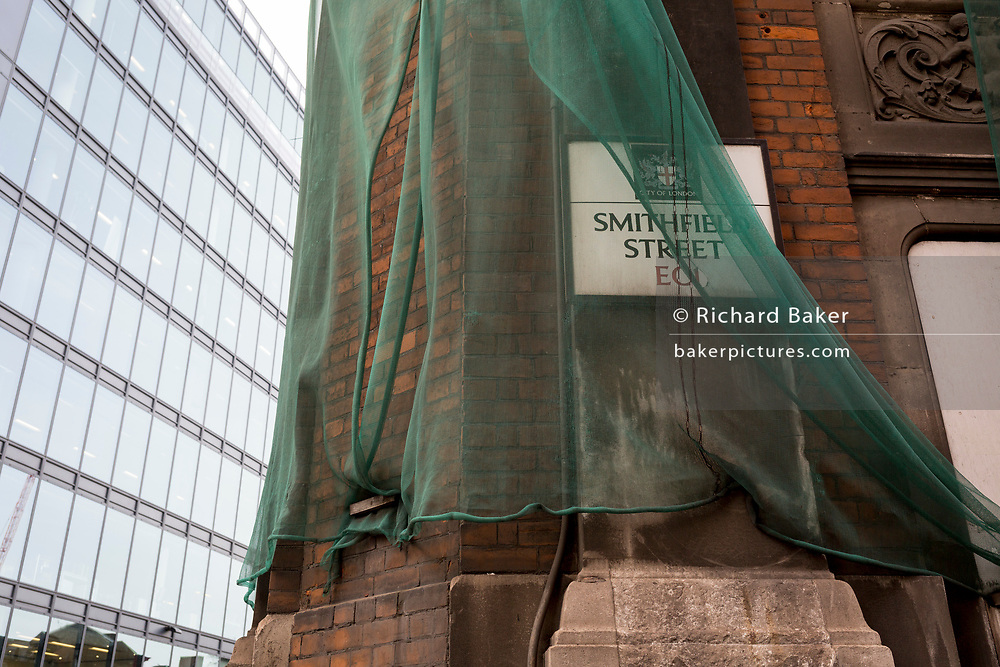 A  detail of constrution safety netting the covers the stonework and masonry in the former Smithfield meat market that is awaiting future redevelopment, on 20th November 2019, at Smithfield in the City of London, England. In March 2015, the Museum of London revealed plans to vacate its Barbican site and move into the General Market Building. The cost of the move is estimated to be in the region of £70 million and, if funding can be achieved, would be complete by 2021. There has been a market on this location since the Bartholomew Fair was established in 1133 by Augustinian friars.