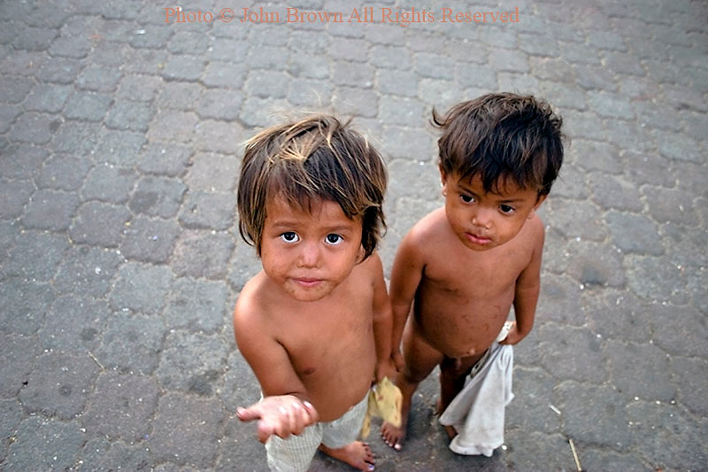Two hungry street children boys living in poverty are in need of food on the streets of Phnom Penh, Cambodia. The World Health Organization estimates that 39% of Cambodia's nearly 15 million people are malnourished.