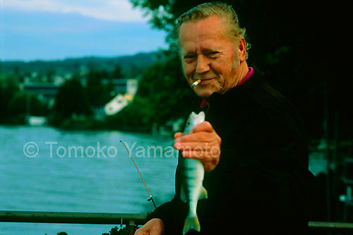 An early morning catch by a proud fisherman who shows off his fish, by  Lake Zurich, Zurichsee, Switzerland.  The photo was taken at the pier of Männedorf, Zurich Canton, Switzerland.