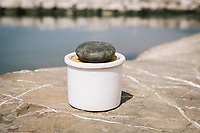 """PISCIOTTA, ITALY - 22 APRIL 2018: A terracotta container with salted Alici di Menaica (Menaica anchovies), with a rock used to pressure the layers of anchovies and salt, is seen here by the harbour in Pisciotta, Italy, on April 22nd 2018.<br /> <br /> Former restaurant owners Donatella Marino and her husband Vittorio Rimbaldo have spent the recent years preparing and selling salted anchovies, called alici di menaica, to a growing market thanks to a boost in visibility from the non-profit Slow Food.  The ancient Menaica technique is named after the nets they use brought by the Greeks wherever they settled in the Mediterranean. Their process epitomizes the concept of slow food, and involves a nightly excursion with the special, loose nets that are built to catch only the larger swimmers. The fresh, red anchovies are immediately cleaned and brined seaside, then placed in terracotta pots in between layers of salt, to rest for three months before they're aged to perfection.While modern law requires them to use PVC containers for preserving, the government recently granted them permission to use up to 10 chestnut wood barrels for salting in the traditional manner. The barrels are """"washed"""" in the sea for 2-3 days before they're packed with anchovies and sea salt and set aside to cure for 90 days. The alici are then sold in round terracotta containers, evoking the traditional vessels that families once used to preserve their personal supply.<br /> <br /> Unlike conventional nets with holes of about one centimeter, the menaica, with holes of about one and half centimeters, lets smaller anchovies easily swim through. The point may be to concentrate on bigger specimens, but the net also prevents overfishing."""
