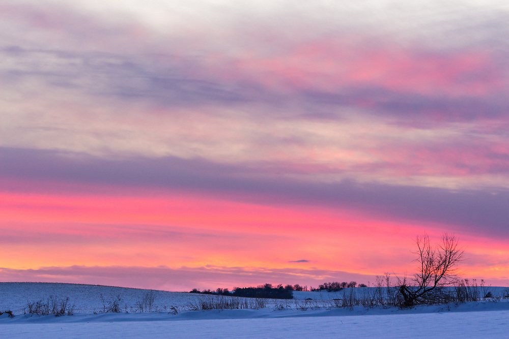 A rosy sunset over snowy farmland.