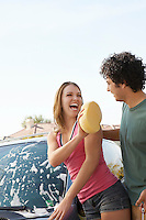 Young couple washing car outdoors
