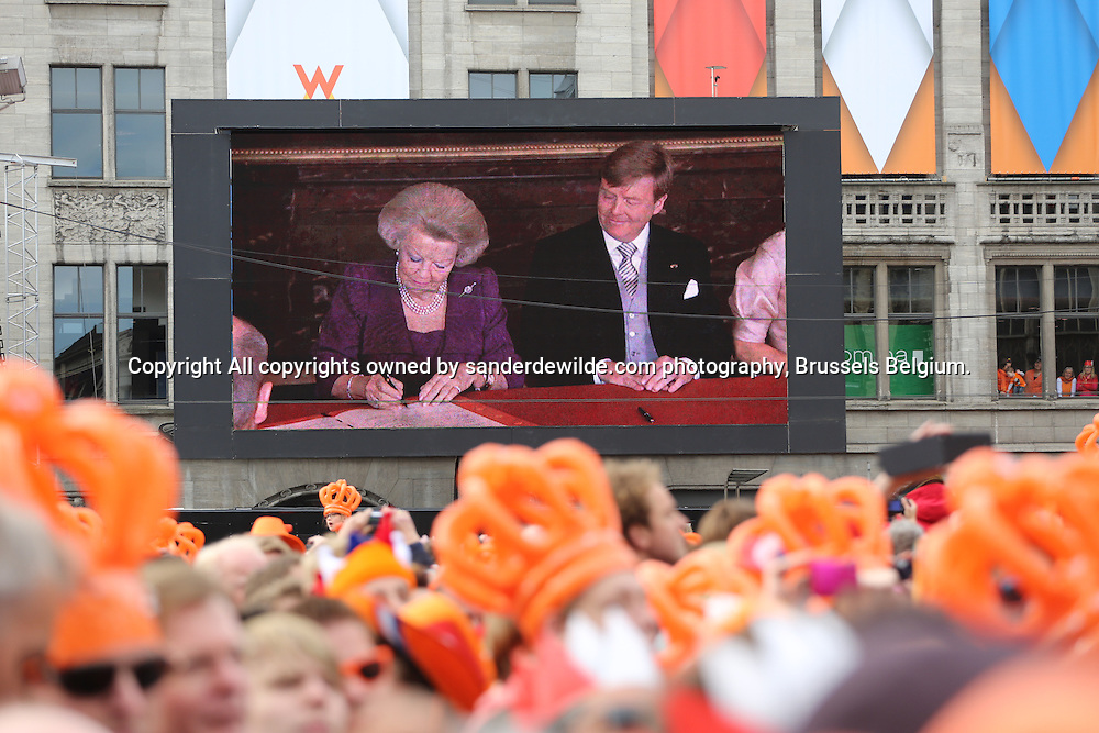 30th April 2013 Amsterdam, Netherlands. Dam Square. Queen Beatrix' abdication takes place, and her son Prince Willem-Alexander will be King of the Netherlands.  Beatrix signs the official papers of the abdication. Thousands of people watch the scene on large tv screens
