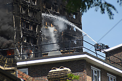 June 14, 2017 - London, United Kingdom - Smoke and flames billows from Grenfell Tower as firefighters attempt to control a blaze at a residential block of flats at Ladbroke Grove. London ambulance confirmed at least six people have died and 64 people have been taken to six different hospitals, 20 in critical conditions, following fire at Grenfell Tower. (Credit Image: © Alberto Pezzali/Pacific Press via ZUMA Wire)