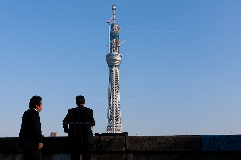 Japanese office workers or  salarymen take in the view of the new Tokyo Skytree from Asakusa, Tokyo, Japan Friday February 4th 2011