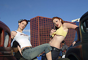 Two sexy Rockabilly girls are posing in front of customised vintage Hotrods cars, Viva Las Vegas Festival, Las Vegas, USA 2006.