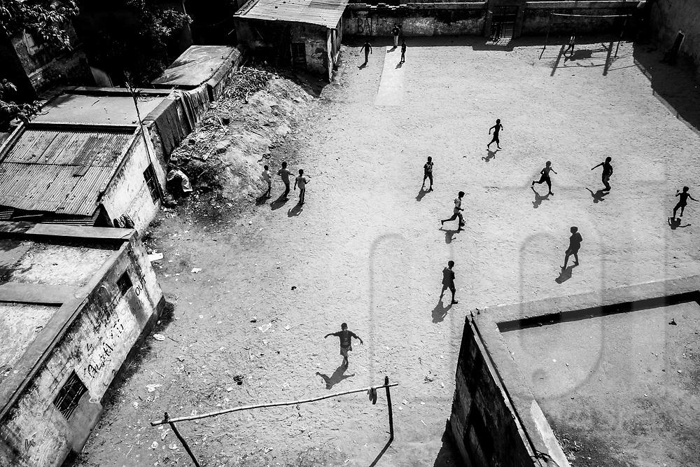 Kids playing soccer on a playground in Dhaka, Bangladesh, Asia
