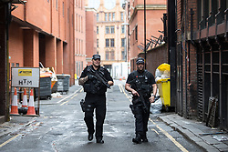© Licensed to London News Pictures . 28/05/2017 . Manchester , UK . Armed police patrol the side streets in Manchester City Centre . The Great Manchester Run 2017 . Security is still heightened in Manchester following a murderous bomb attack at an Ariana Grande gig at Manchester Arena on Monday 22nd May . Photo credit : Joel Goodman/LNP