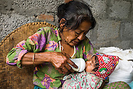 Bhagawati Baniya (56) bottle feeds her youngest grand daughter Sapana Baniya (2 months) in their temporary home in Chautara, Sindhupalchowk, Nepal on 29 June 2015. The three girls lost their mother during the April 25th earthquake that completely levelled their house. Aastha was buried under the rubble together with her mother but Aastha survived. As their father Ratna Baniya (28) cannot care for the children on his own, SOS Childrens Villages has since been supporting the grandmother with financial and social support so that she can manage to raise the children comfortably and ensure that they will all be schooled. Photo by Suzanne Lee for SOS Children's Villages