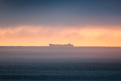 © Licensed to London News Pictures. 01/10/2015. Whitby, UK. Picture shows a large vessel passing the Whitby coastline in this mornings fog. The fishing town of Whitby awoke to a thick covering of fog but the weather is due to brighten up later today. Photo credit: Andrew McCaren/LNP