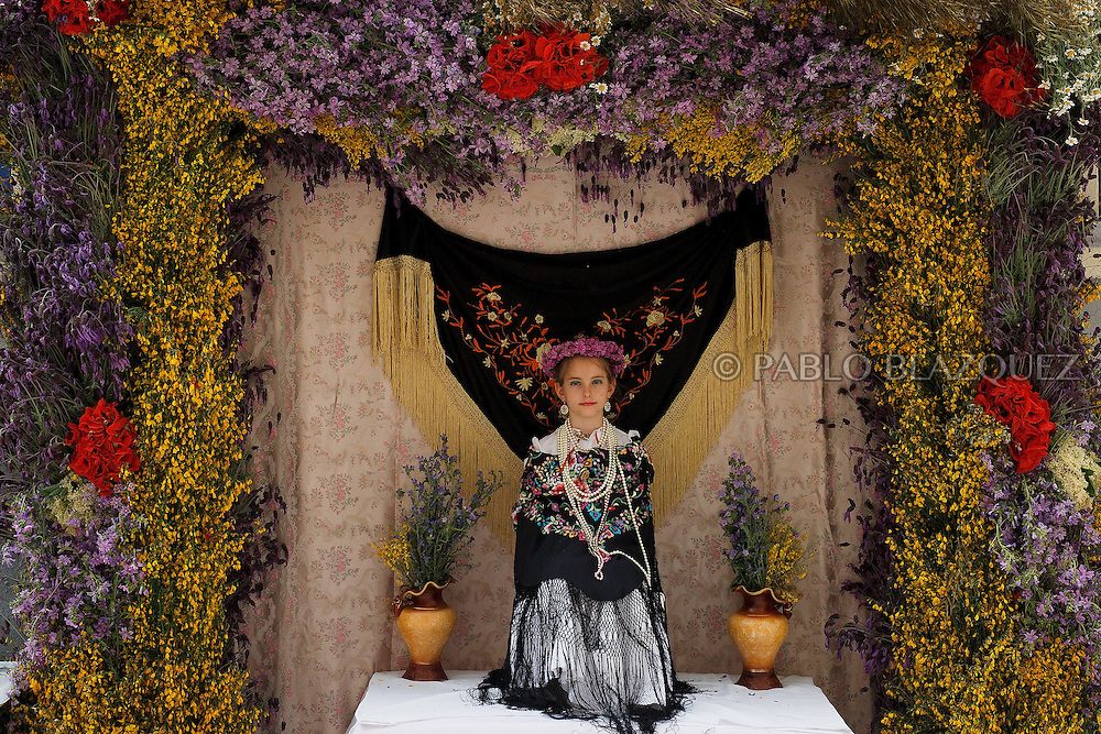 A 'Maya' girl sits on the altar during the 'La Maya' tradition in the streets around the San Lorenzo church on May 10, 2015 in Lavapies neighborhood, Madrid, Spain. 'La Maya' festivity is a pagan tradition to celebrate the beginning of the spring which is believed to come from the medieval age. In old times the 'Maya's Festival' used to take place at The 'Mayas' field' (Prado de las Mayas) which is where now the San Lorenzo church is located. La Maya combines symbols of fertility and prosperity on agriculture and shepherding economy. A 'Maya' girl dressed with traditional customs sits on an altar in the street decorated with flowers, plants and cushions. Other Mayas and Mayos offer flowers, traditional sweets, lemonade, and wine to members of the public as they play music and dance. (© Pablo Blazquez)