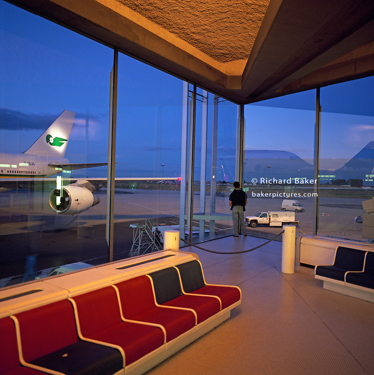 A lone passenger gazes out from the departure lounge at Charles de Gaulle/Roissy airport terminal to where airliners are parked. It is late evening and blue light outside makes the orange interior look warm. Designed by Paul Andreu, Charles de Gaulle became a symbol for airport modernity - a Le Corbusier concept of rail stations and ?autodromes.? Charles de Gaulle?s role as airport and rail station fuses into one, thus becoming an ?Aérogare? where trains and planes whisk the new world traveller of the late ?60s, away beyond an ever-extending horizon. From here, the Air France Concorde crashed on the aviation employment town of Gonesse on July 25th 2000. Picture from the 'Plane Pictures' project, a celebration of aviation aesthetics and flying culture, 100 years after the Wright brothers first 12 seconds/120 feet powered flight at Kitty Hawk,1903. .