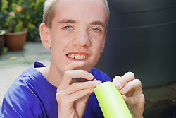 Portrait of teenage boy with autism playing with toy,