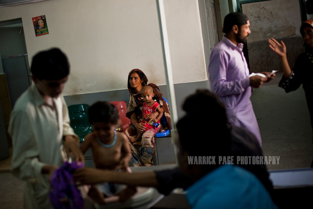 JAMSHAROO, PAKISTAN - OCTOBER 13: Noor Bano, 35, waits to see a doctor with her son, Mohammad Ali, 2, in the OPD of Jamsharoo Civil Hospital, on October 13, 2011, in Jamsharoo, Pakistan. Doctors did not think Mohammad would survive when he was admitted to the NSC two months ago with severe malnutrition brought on by TB and pneumonia. Extreme poverty, poor diet and health, exposure to disease, and inadequate sanitation and hygiene annually produce alarming levels of malnutrition amongst children, but the floods of 2010 and 2011 have increasingly endangered an already vulnerable population. Child malnutrition has breached emergency levels in Pakistan - particularly Sindh province - after monsoon floods devastated the country's poorest region for a second year. Malnourishment It is the single biggest contributor to under-five mortality, increasing the risk of infections and slowing recovery from illness. It stuns both mental and physical growth and their future capacity, sapping the next generation's ability to meet the demands of a country already facing an unstable future. According to UN reports, hundreds of thousands of children in Pakistan suffer from severe-acute-malnutrition, with 15.1% of children experiencing acute malnourishment. The Economist recently reported that 44% of children in Pakistan suffer from varying degrees of malnutrition. (Photo by Warrick Page)