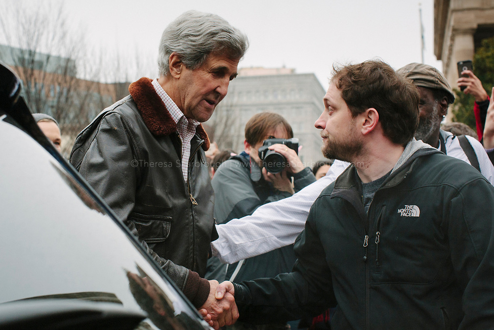 Former Secretary of State John Kerry (left) shakes hands with a man during the Women's March on Washington, D.C., January 21, 2017