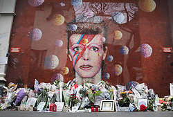 © Licensed to London News Pictures. 10/01/2017. London, UK. Floral tributes are placed at a mural and shrine to David Bowie in Brixton. David Bowie who died a year ago today, was born in Brixton, south London. Photo credit: Peter Macdiarmid/LNP