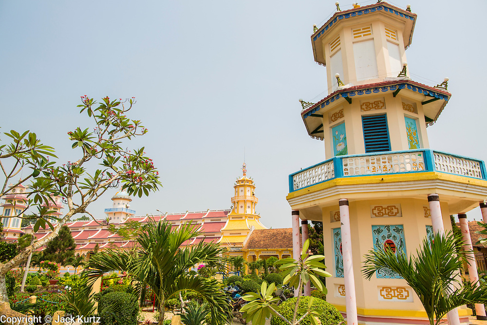 """29 MARCH 2012 - TAY NINH, VIETNAM:    A tower on the campus of the Cao Dai Holy See in Tay Ninh, Vietnam. Cao Dai (also Caodaiism) is a syncretistic, monotheistic religion, officially established in the city of Tây Ninh, southern Vietnam in 1926. Cao means """"high"""" and """"Dai"""" means """"dais"""" (as in a platform or altar raised above the surrounding level to give prominence to the person on it). Estimates of Cao Dai adherents in Vietnam vary, but most sources give two to three million, but there may be up to six million. An additional 30,000 Vietnamese exiles, in the United States, Europe, and Australia are Cao Dai followers. During the Vietnam's wars from 1945-1975, members of Cao Dai were active in political and military struggles, both against French colonial forces and Prime Minister Ngo Dinh Diem of South Vietnam. Their opposition to the communist forces until 1975 was a factor in their repression after the fall of Saigon in 1975, when the incoming communist government proscribed the practice of Cao Dai. In 1997, the Cao Dai was granted legal recognition. Cao Dai's pantheon of saints includes such diverse figures as the Buddha, Confucius, Jesus Christ, Muhammad, Pericles, Julius Caesar, Joan of Arc, Victor Hugo, and the Chinese revolutionary leader Sun Yat-sen. These are honored at Cao Dai temples, along with ancestors.    PHOTO BY JACK KURTZ"""