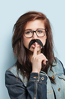 Portrait of young woman with fake mustache and finger on her lips against light blue background