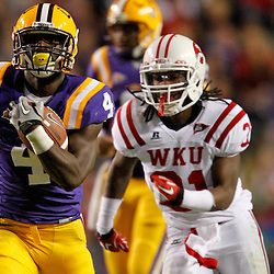 November 12, 2011; Baton Rouge, LA, USA; LSU Tigers running back Alfred Blue (4) breaks away from Western Kentucky Hilltoppers linebacker Terran Williams (31) for a touchdown during the second half of a game at Tiger Stadium.  Mandatory Credit: Derick E. Hingle-US PRESSWIRE