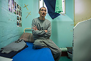 A prisoner sitting on the bed in his single cell. HMP/YOI Portland, Dorset. A resettlement prison with a capacity for 530 prisoners. Portland, Dorset, United Kingdom.