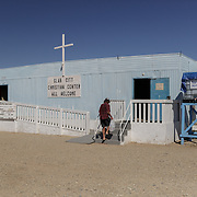 The Slab City Christian Center is run by Pastor Smiley, an ex-Marine, who was given the congregation three years prior by Pastor Phil. Because Slab City is completely off the grid - no water, electricity or sewers, Smiley has limited water available for residents in need as the temperatures climb to 125F. Smiley is letting Paul Lineberger live in the kitchen trailer, seen here walking inside.
