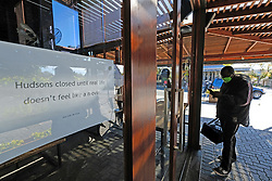 JOHANNESBURG SOUTH AFRICA - MAY 01 A delivery driver waits as Hudsons Parkhurst staff prepare food for delivery on May 01, 2020 in Johannesburg South Africa. South Africa moved down to Level 4 of the national lockdown with relaxed restrictions as part of a risk adjusted 5 stage phasing of lockdown measures. This includes allowing of certain restaurants to reopen for trade and prepare hot food as delivered takeaway only. (Photo by Gallo Images/ Dino Lloyd)
