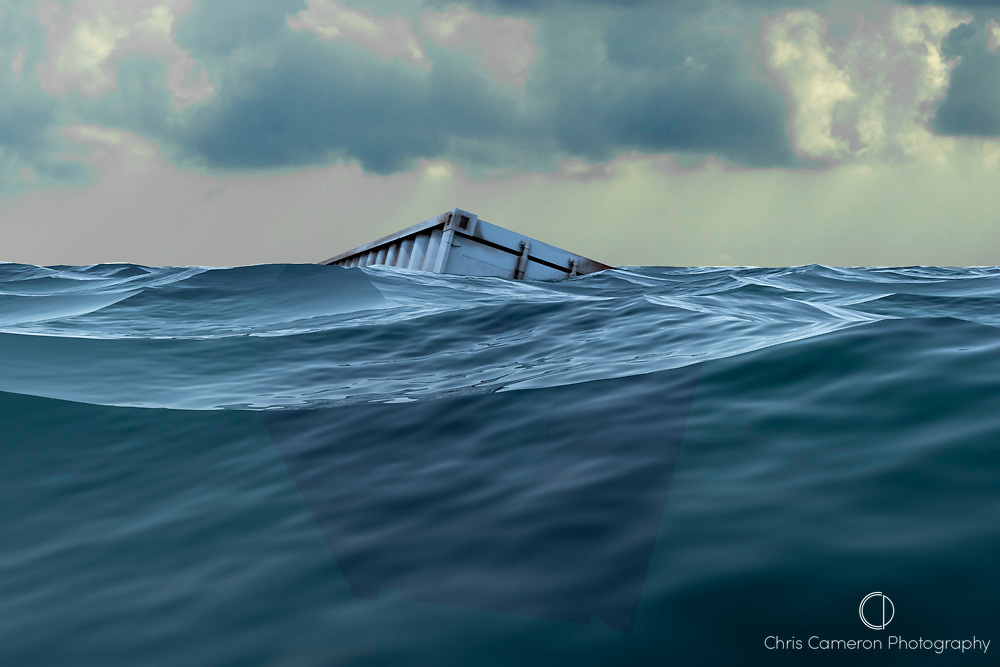 Shipping container partly submerged at sea.