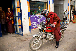 Tibet New Year - China - Edward Wong<br /> A monk from Rongwo monastery  (Longwu in Chinese) gets on his motor cycle in Rebkong (Tongren in Chinese), Qinghai province in China, February 24, 2009. Photo by Shiho Fukada for The New York Times