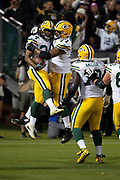 Green Bay Packers running back Joel Bouagnon (34) leaps in the air as he celebrates with Green Bay Packers offensive guard Adam Pankey (77) after scoring a third quarter touchdown nullified by an offensive penalty during the 2018 NFL preseason week 3 football game against the Oakland Raiders on Friday, Aug. 24, 2018 in Oakland, Calif. The Raiders won the game 13-6. (©Paul Anthony Spinelli)