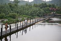 Family crossing a bridge to Sunny Park in  Anji, China 2009.