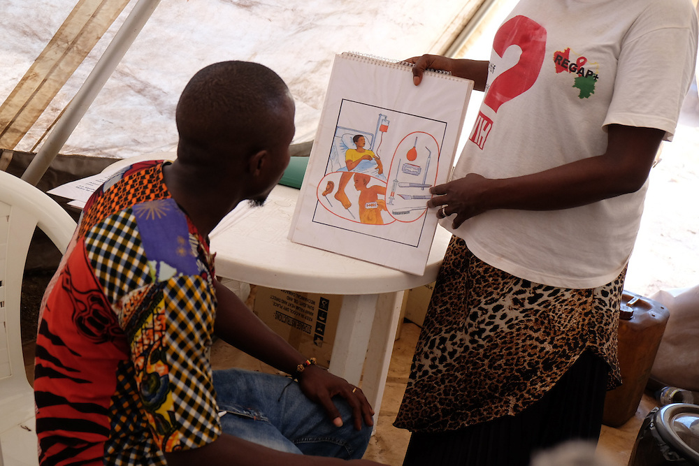 Mohamed Camara listens as a HIV activist undertakes an awareness session on HIV transmission at the MSF mobile clinic in the neighbourhood of Sangoyah Market, Conakry, Guinea on March 17, 2016. MSF launched a HIV testing campaign in Conakry with the support of health authorities moving throughout several neighbourhoods throughout 2016.<br /> <br /> Despite countries in West and Central Africa having a relatively low HIV prevalence (