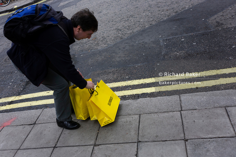A shopper picks up purchases in yellow Selfridges bags in London's West End. The bags are one of the capital's most striking symbols of British retail and are seen across the city as splashes of vibrant colour on the otherwise drab pavements and streets. The economic recovers appears to have begun in earnest and retail therapy has attracted these Londoners to the West End, away from the larger, warmer shopping Malls on the outskirts of town. Selfridges was founded by Harry Gordon Selfridge. The flagship store in London's Oxford Street is the second largest shop in the UK (after Harrods) and was opened on 15 March 1909.
