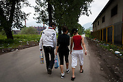 Dino, Endriana and Dina walk pass a row of Roma family homes on their way back from buying groceries.